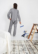 Man with paint roller looking at white wall