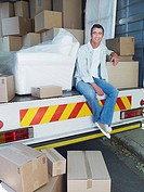 Smiling man sitting in moving van with cardboard boxes