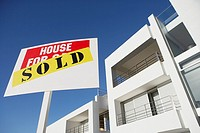 Low level view of sold sign in front of house with blue sky