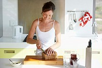 Woman in kitchen slicing bread