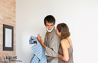 Woman and man with shaving cream on face in bathroom
