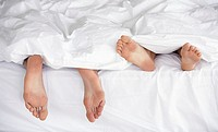 Male and female feet in bed under blankets
