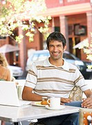Man at outdoor cafe with laptop