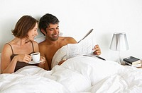 Man and woman in bed with newspaper and coffee