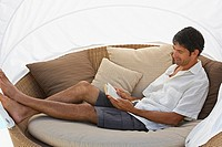 Man reclining on chair reading book