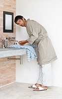 Man in robe washing face