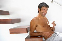 Shirtless man sitting on stairs with mug