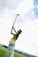 Young woman swinging golf club, rear view