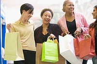Multi-ethnic women holding shopping bags
