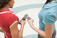 Multi-ethnic teenage girls using cell phones