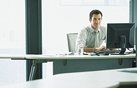 Businessman sitting at desk with computer working and smiling