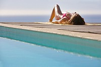 Woman sunbathing on pool deck