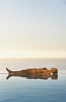 Woman lying down in bikini on edge of infinity pool
