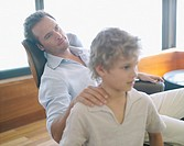 Father relaxing with hand on son's shoulder at home