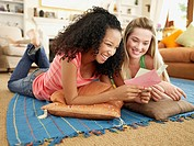 Two teenage girls lying down on floor looking at note card with envelope smiling