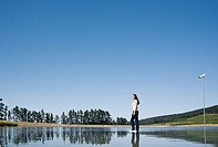 Woman standing on water with surveillance camera and trees