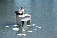 Businesswoman at desk in water with paperwork floating away