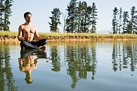 Man doing yoga on water with trees