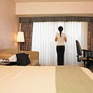 Asian businesswoman looking out hotel window