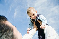 ´Father lifting son 12-15 months in air, low angle view´