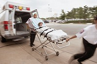 Blurred motion shot of EMTs wheeling gurney with patient away from ambulance