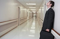 Businessman leaning against wall in hospital hallway