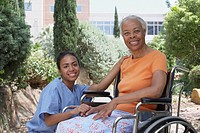 African female nurse smiling with senior female patient in wheelchair