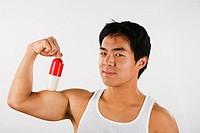 Asian man holding pill on flexed biceps