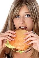 Woman bites into a hamburger