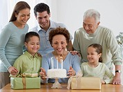 Senior Hispanic woman celebrating birthday with family