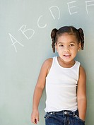 African girl leaning against blackboard