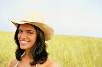 Woman wearing straw hat in field