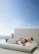 Man and woman lying down on bed outdoors with blue sky