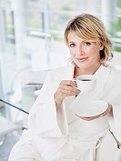 Woman in bathrobe in glass room with coffee smiling