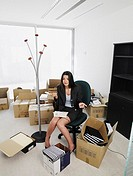 Female office worker holding phone while sitting in a new office surrounded by boxes