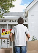 Rear view of man with cardboard boxes standing in front of house with sold sign