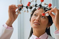 Asian female scientist looking at model of chemical compound