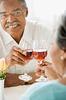 Senior African couple toasting with wine