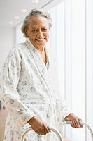 Senior African woman in bathrobe using walker