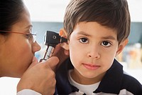 Hispanic female doctor examining boyÆs ear