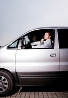 Businessman talking on the phone while driving in the car