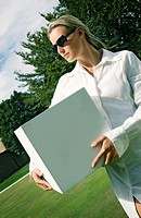 Businesswoman with sunglasses carrying a box