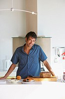 Man in kitchen with bread and baking smiling
