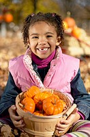 African girl holding basket of pumpkins
