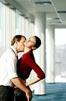 Businessman hugging and kissing businesswoman