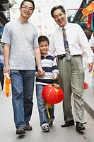 Asian grandfather, father and son walking on sidewalk