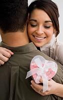 Hispanic woman holding gift and hugging boyfriend