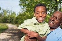 African grandfather holding grandson in park