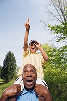 African grandfather carrying grandson on shoulders using binoculars in park