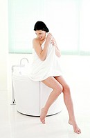Woman sitting on the bathtub corner wiping her hair with towel